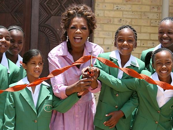 epa01150920 (ФАЙЛОВЕ) Това изображение на файл от 2 януари 2007 г. показва водещата на токшоу в САЩ Опра Уинфри (С), прерязваща лентата с някои от момичетата, които са записали училището, финансирано от Уинфри в Хенли на Клип, Южна Африка, вторник, 02 януари 2007. Ръководителят на училището е отстранен на фона на твърденията за сериозни нарушения, тъй като местните и американските следователи са били привлечени за разследване на предполагаем тормоз EPA / KIM LUDBROOK