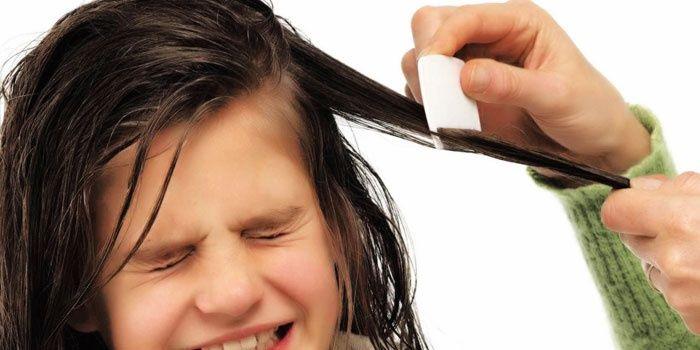 Момиче, сресващо косата си с малък гребен